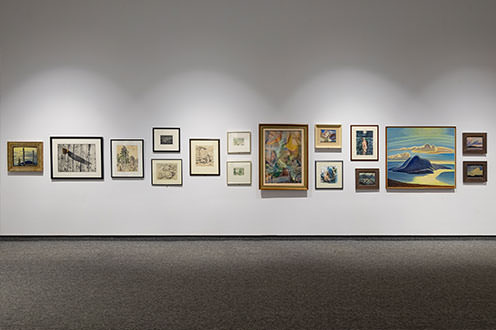 A wall at the Tom Thompson Art Gallery lined with different sized art peices in unique frames.
