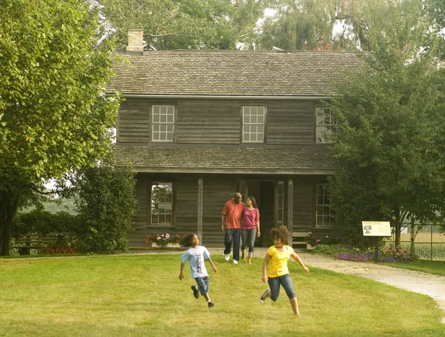 Two adults and two children playing in front of a historic building