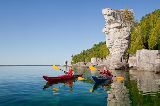Deux femmes pagayant des kayaks par une belle journée