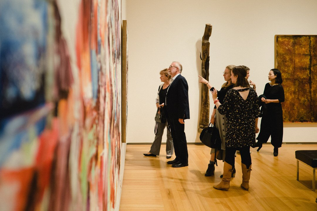 Groups of viewers commenting animatedly on painting beside enormous colourful painting