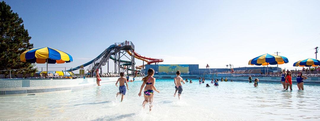 Les enfants en maillot de bain s'amusent dans la piscine pendant que les sauveteurs surveillent les enfants