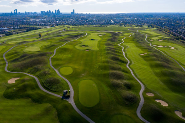 Aerial view of green grass with elevations and holes and sand traps and and pathways