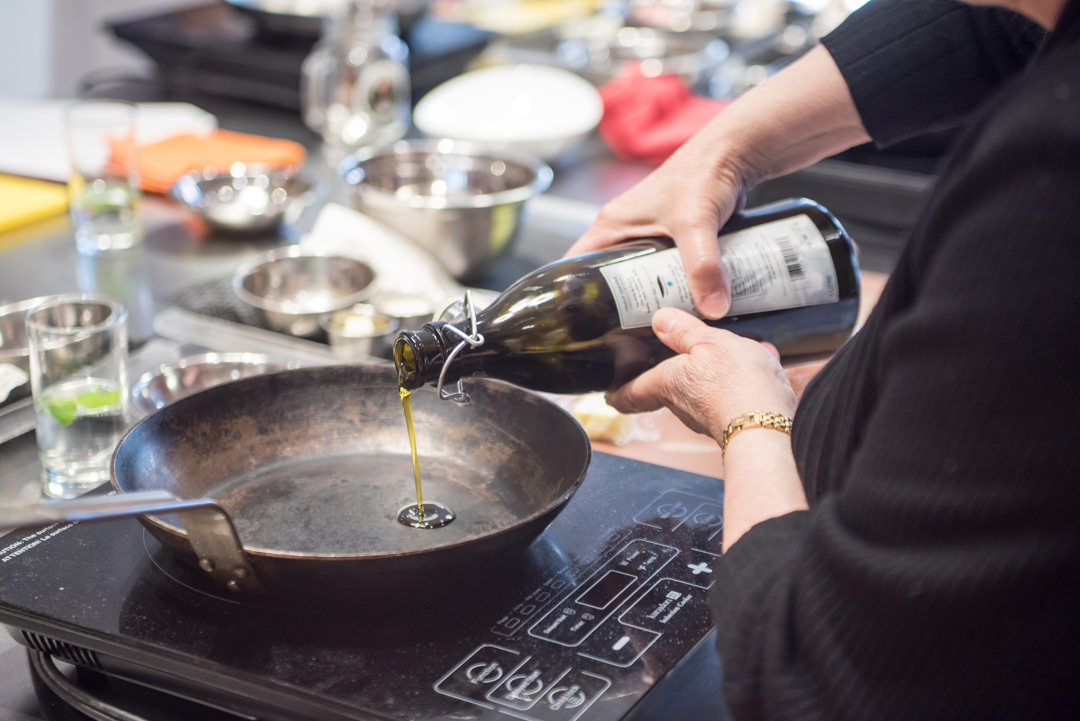 Hands pouring oil from bottle into metal frying pan on one-burner stove
