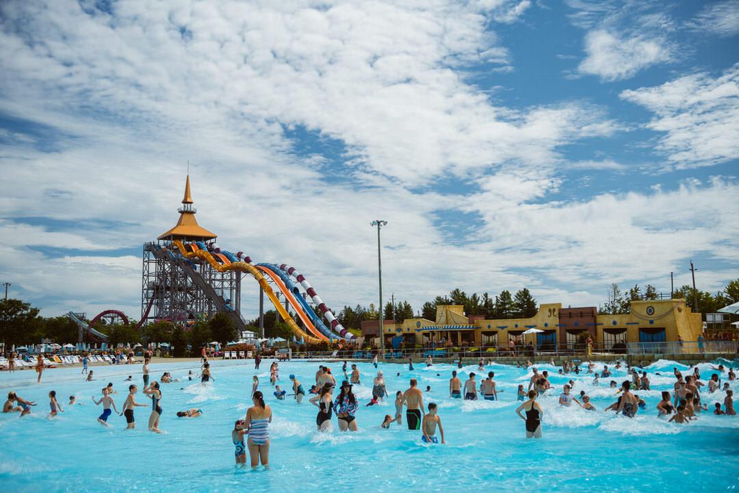 Grande piscine remplie d'adultes et d'enfants avec glissades d'eau de l'autre côté.
