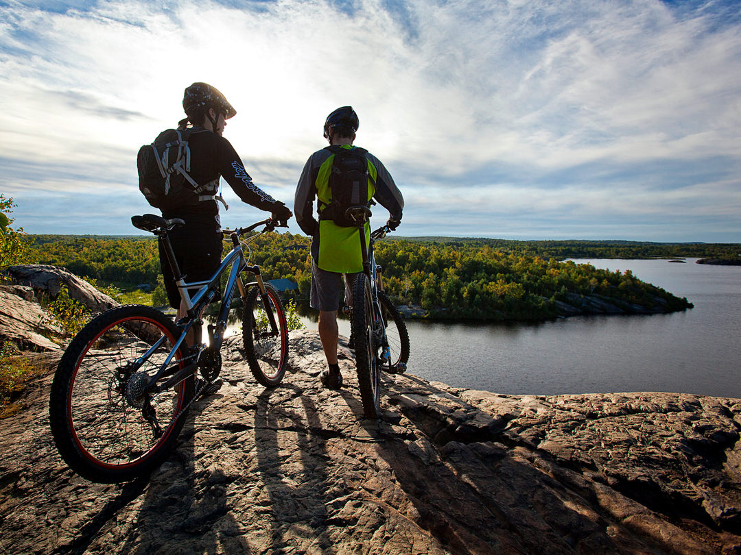 Two cyclists stand on the edge of a rock overlooking a scenic bay