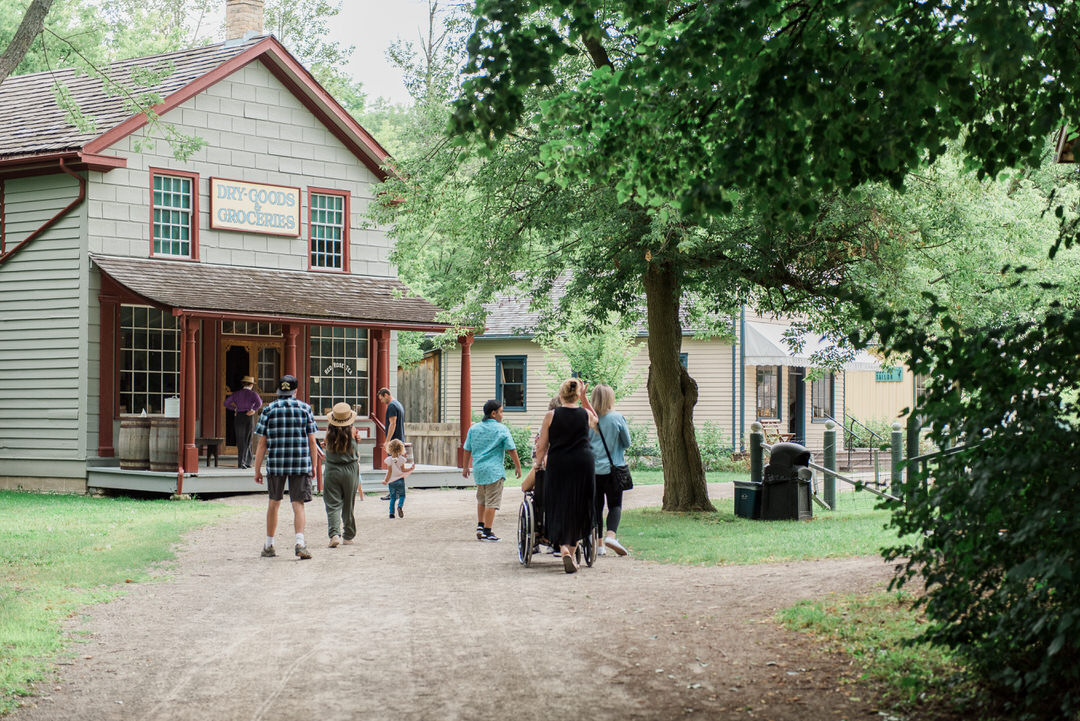 Visitors walking along pathway into and past heritage Dry Goods & Groceries store