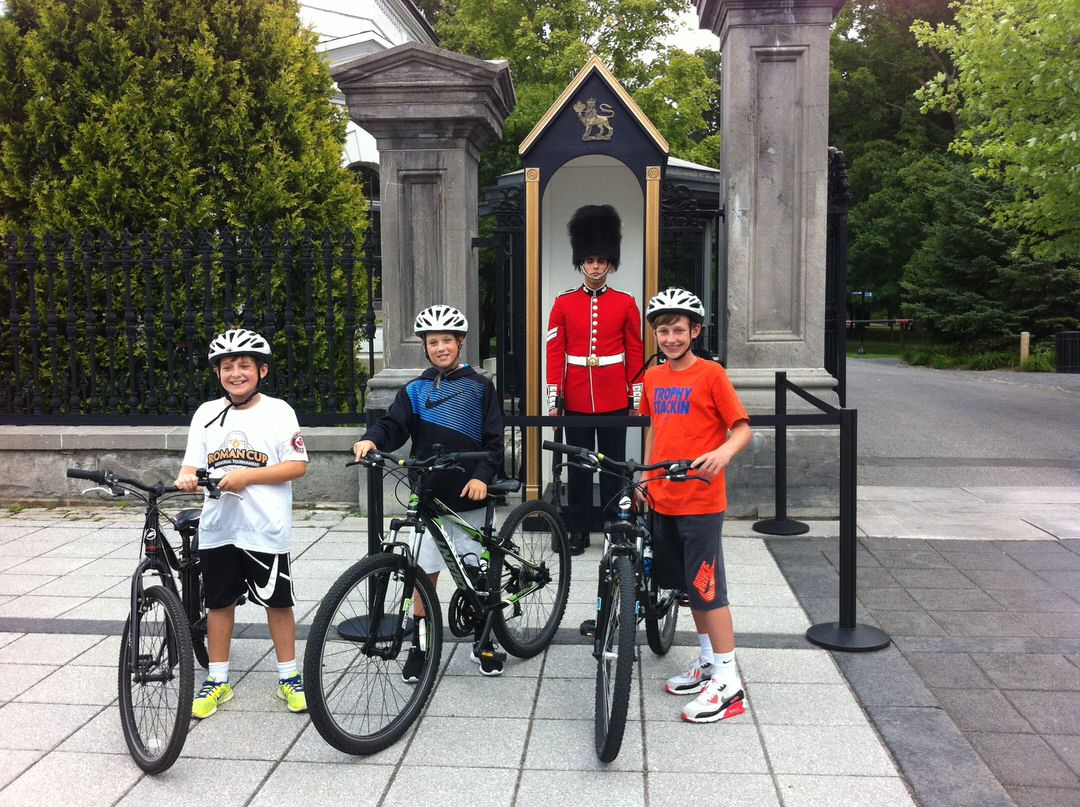 3 young smiling kids walking their bicycles past RCMP sentry stationed between 2 stone pillars