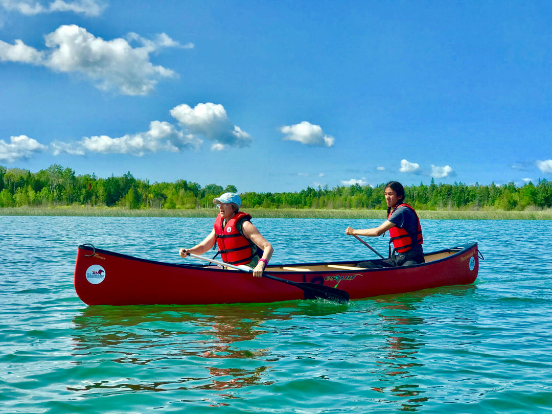 2 canoeists paddling on expanse of water along forested shore