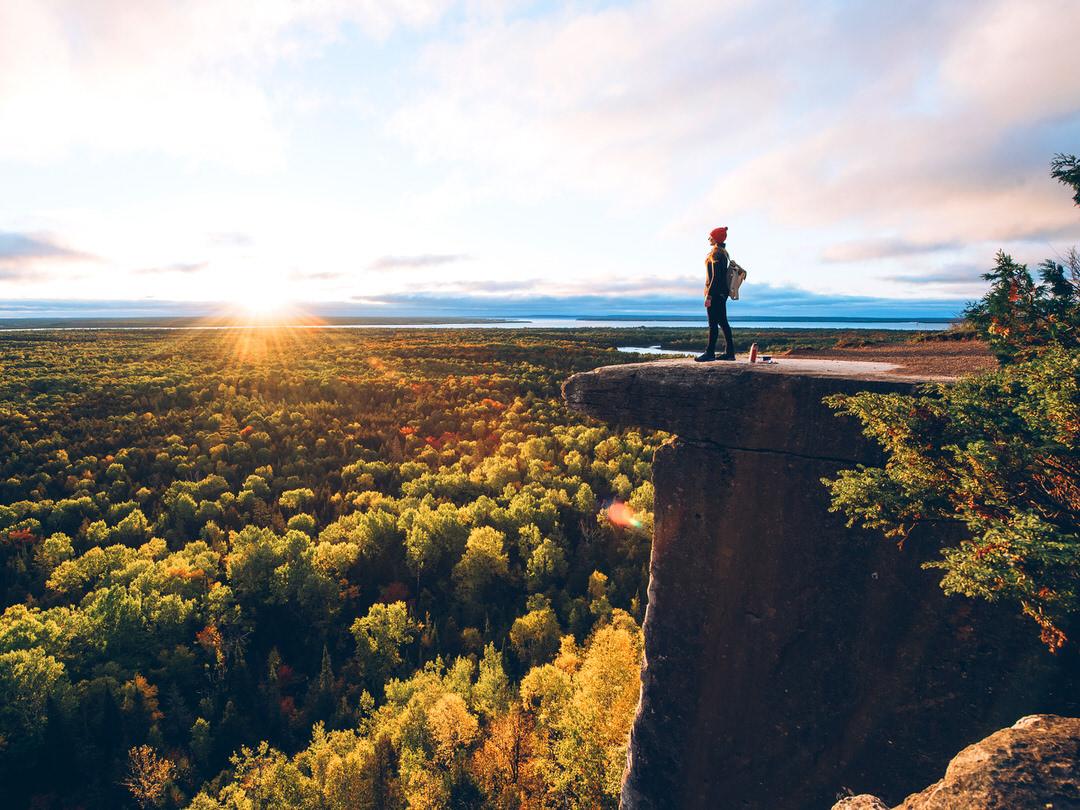 Une femme se tient sur un affleurement rocheux surplombant un paysage pittoresque aux couleurs de l'automne