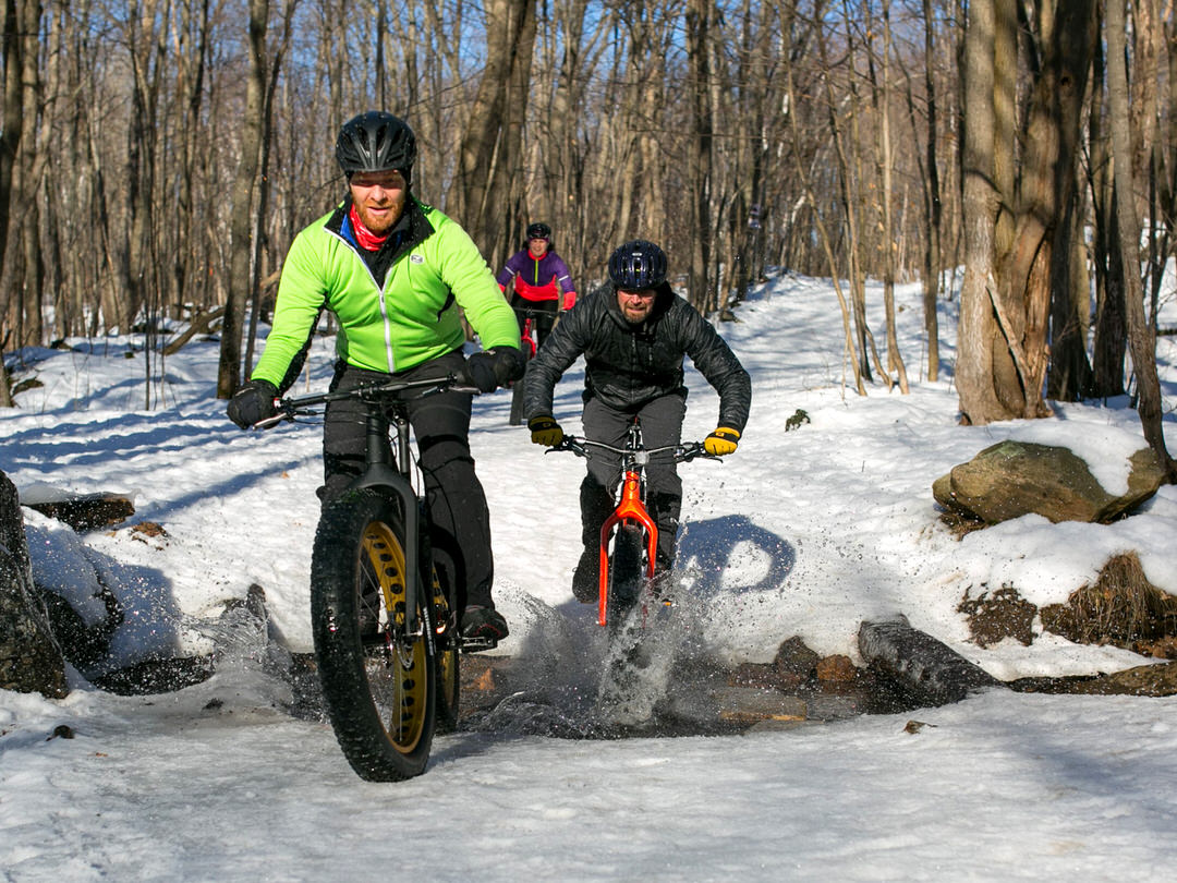 Three cyclists ride along a snowy trail on fat bikes