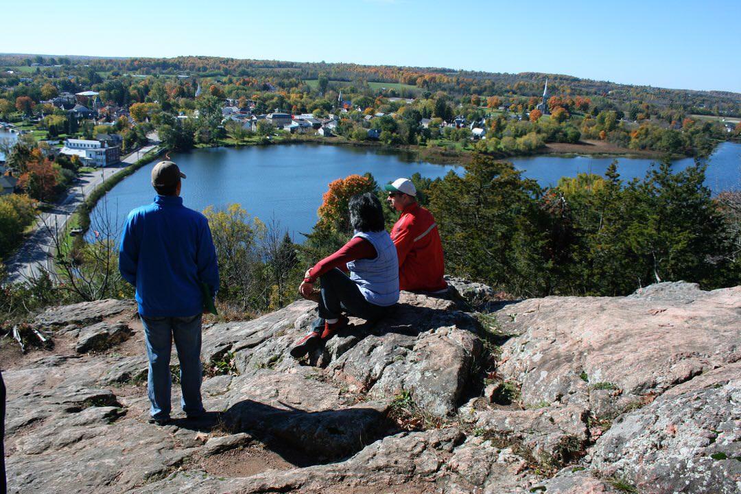 Trois visiteurs debout et assis sur un rocher brut surplombant le lac Upper Rideau et la municipalité de Westport plus bas.