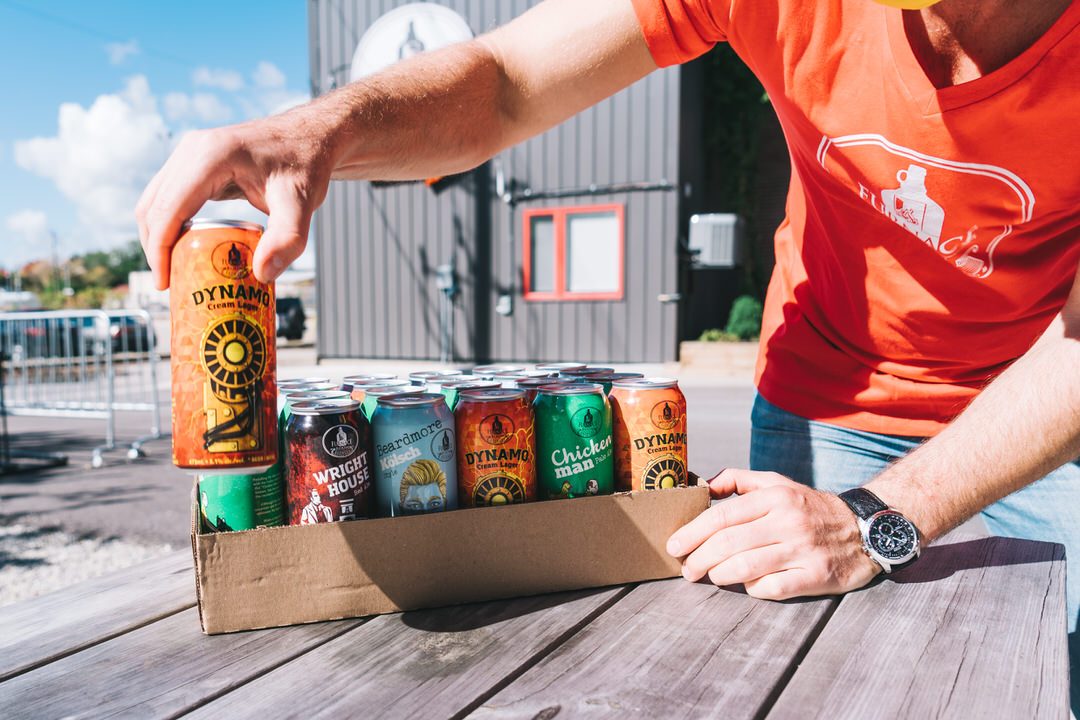 Gentleman packing cans of various kinds of beer outside brewery building