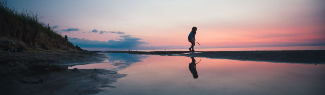 A child playing with a stick on a beach during the pink sunset filled sky