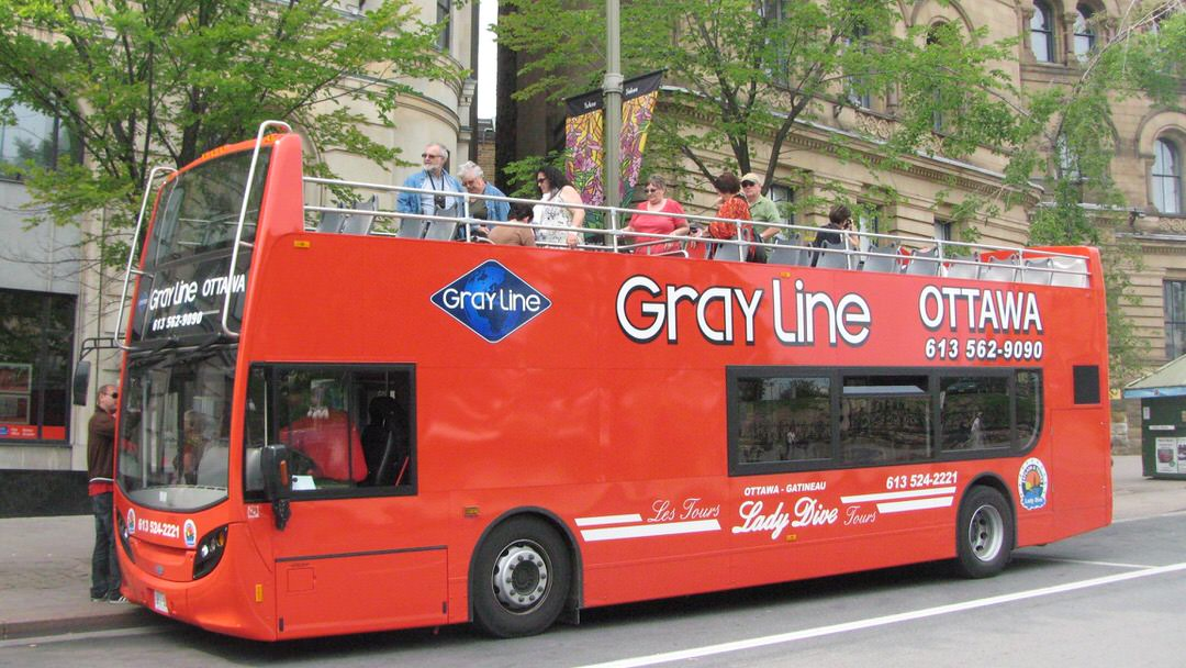 Red Gray Line double-decker bus parked on historic street with sightseers on upper level