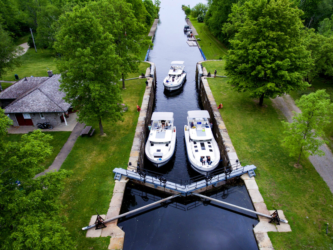 Two vessels navigate locks along the Rideau Canal