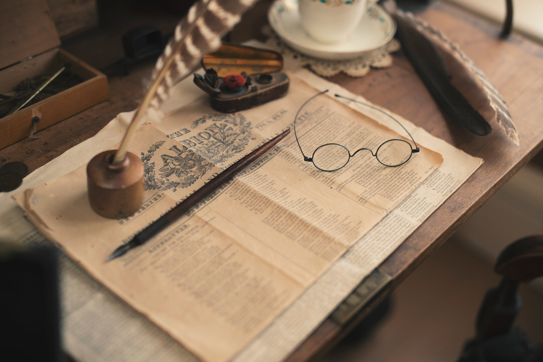 Table with china cup and saucer beside front page of historic newspaper with heritage pens and reading glasses on top