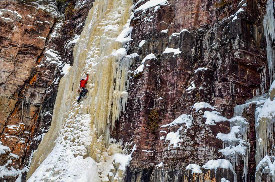 A man ice climbing a tall frozen waterfall