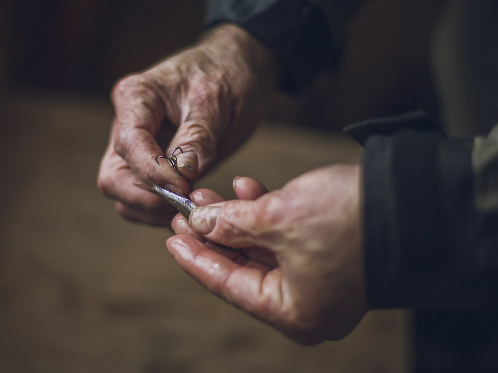 Close up of an angler's hands tying a lure to his fishing line
