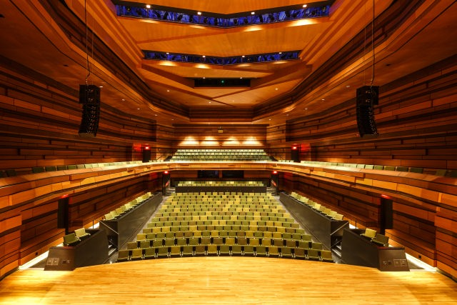 Concert hall stage facing rows of seats to the back with carved wood ceiling with soft lighting