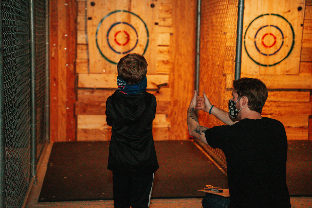 Squatting man facing dartboard painted on wood wall at back showing young boy how to aim