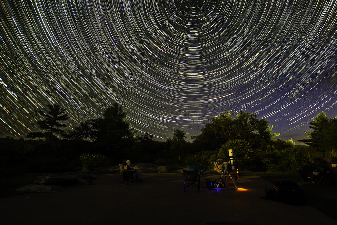 Public telescope facing background woods overwhelmed by dark sky with hundreds of brilliant parallel circular star paths