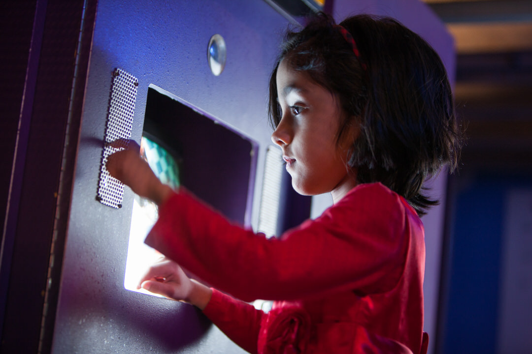 Small child standing in front of recessed computer screen pressing dots on small metal plate on the wall to her left