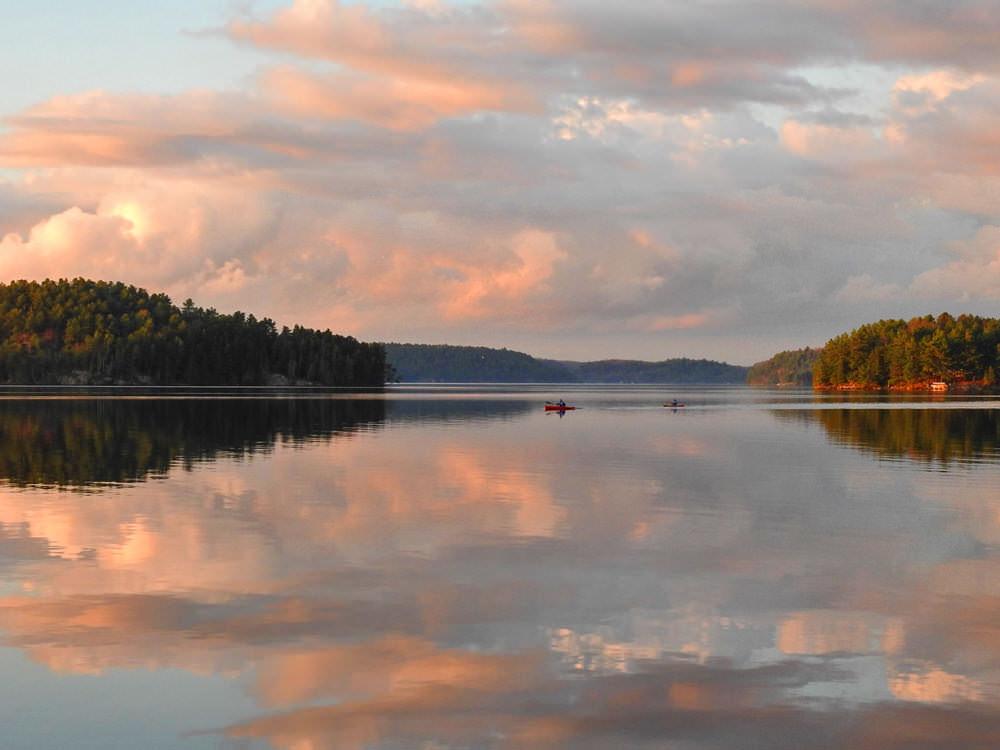 Deux kayakistes traversent un lac au coucher du soleil