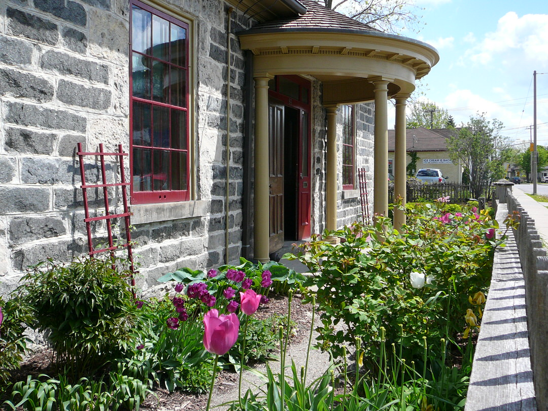 Angle view of old gray brick building with portico at front entrance and tulip garden along front wall