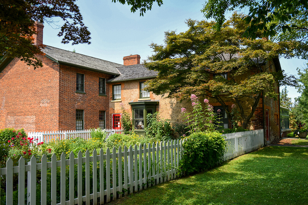 Parallel white picket fences enclosing flower garden and trees extending back to large L-shaped old brick house