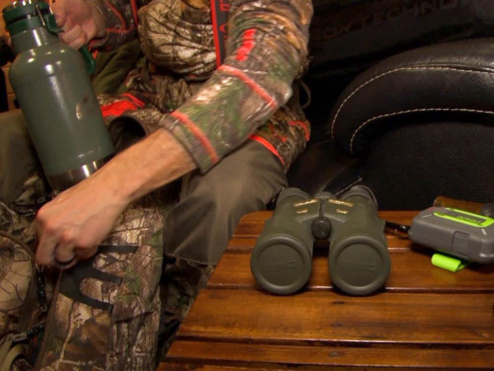 Un homme vêtu de camouflage emballe des jumelles, un thermos et d'autres équipements de chasse