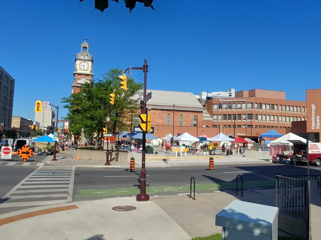 Downtown sidewalk with people shopping outdoors at canvas-covered kiosks on far side of street in and around large town square