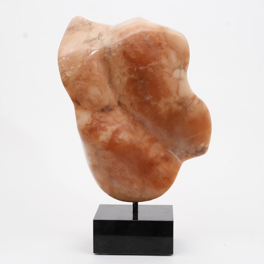 Abstract sculpture in shades and tints of brownish-pink with rounded edges and graceful curves mounted on rectangular black pedestal