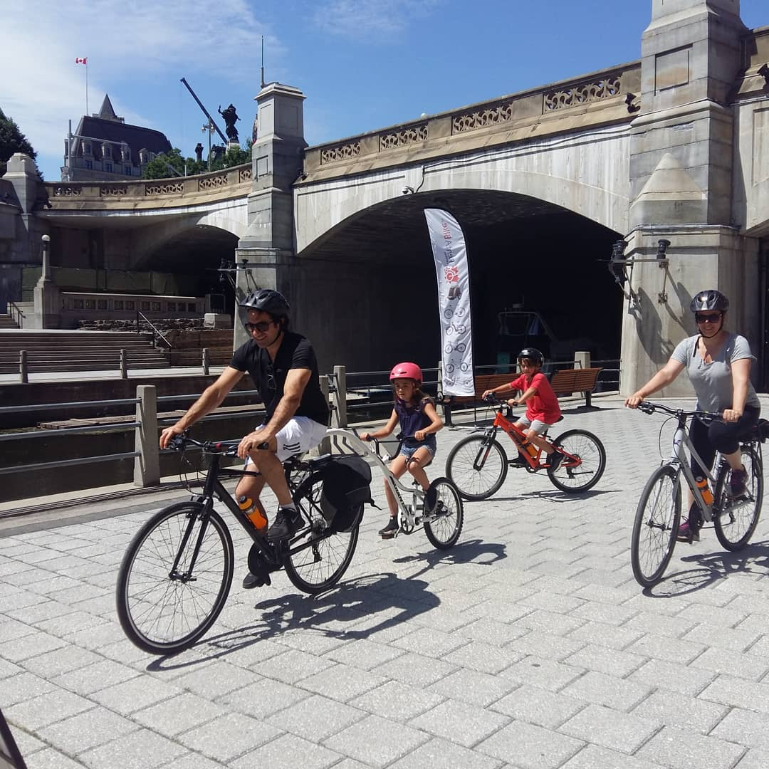 Man and woman and 2 children riding bicycles on wide grey brick path passing high bridge with heritage railings