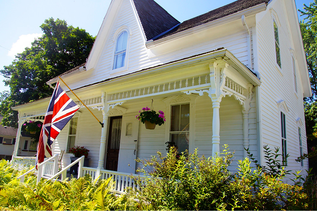 Large old white clapboard house with rectangular white portico across front projecting Canadian flag flying over front gardens
