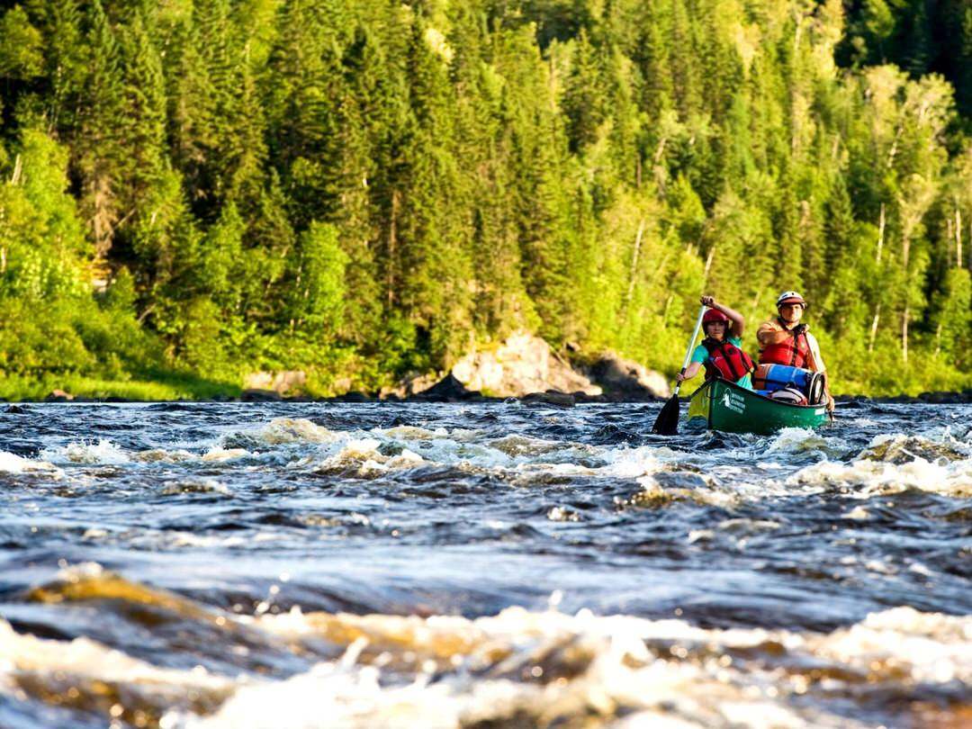 Two paddlers canoe through rushing rapids in a wilderness river