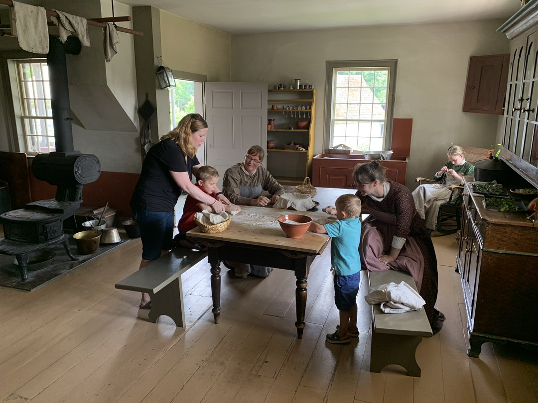 3 women in long pioneer dresses with 2 of them at kitchen table helping modern woman and 2 small boys knead bread dough