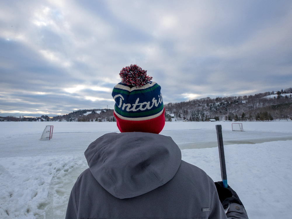 A young man stands in front of a pond ice hockey rink holding a hockey stick
