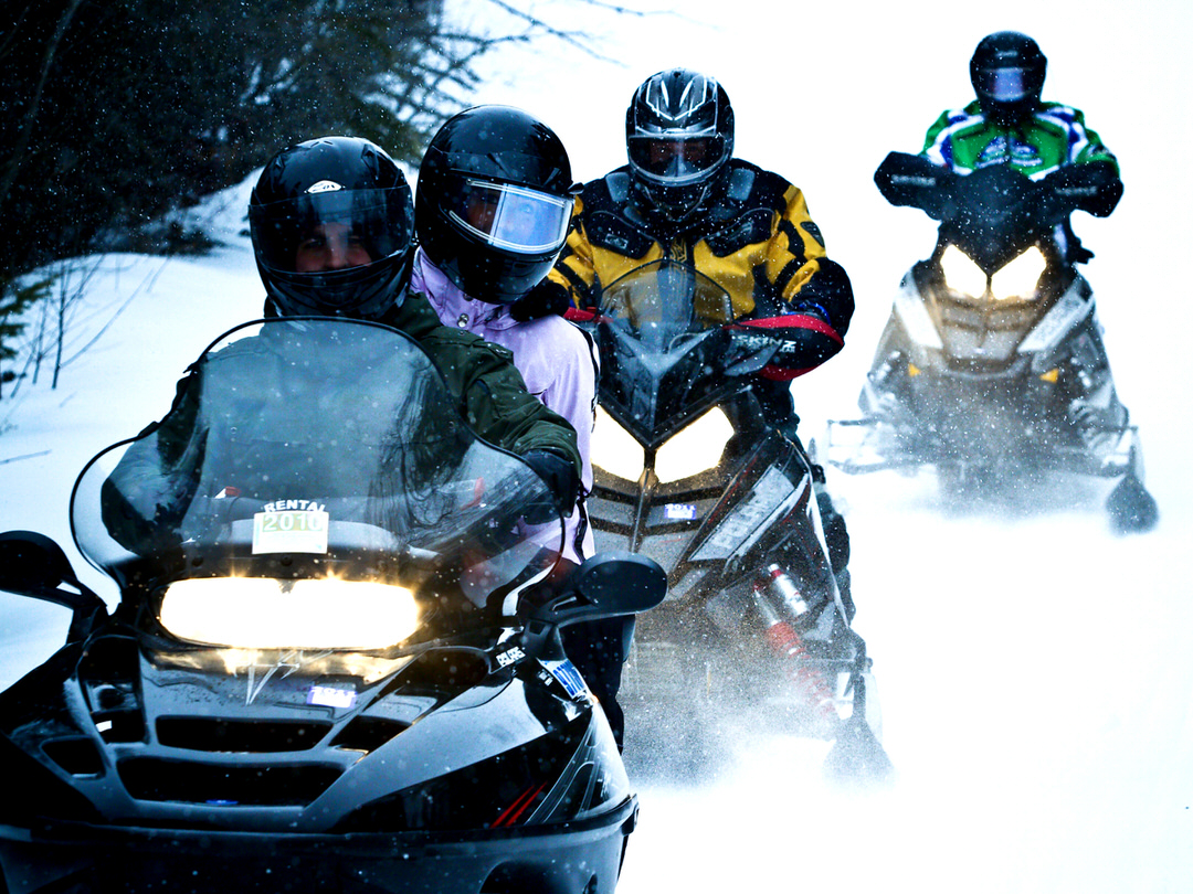 People riding on snowmobiles