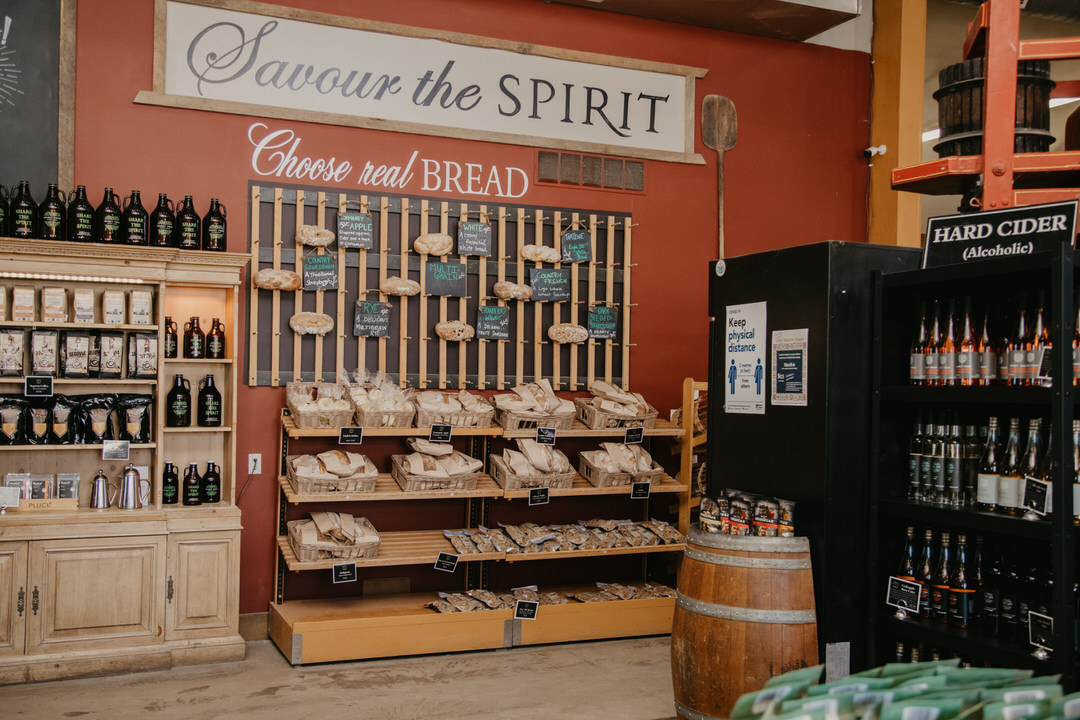 Corner inside store with small barrel in front and shelves on both walls of cider bottles and homemade bread and other bottles