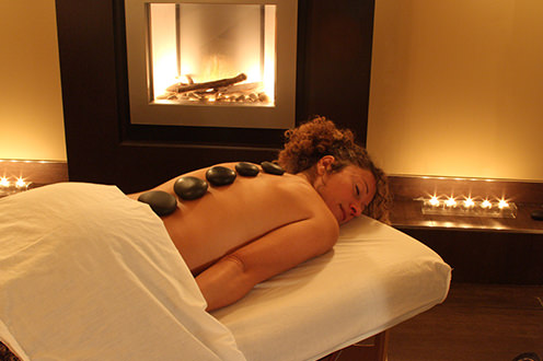 Woman lying on stomach on massage table under sheet with eyes closed and 5 large smooth brown stones spaced along her spine