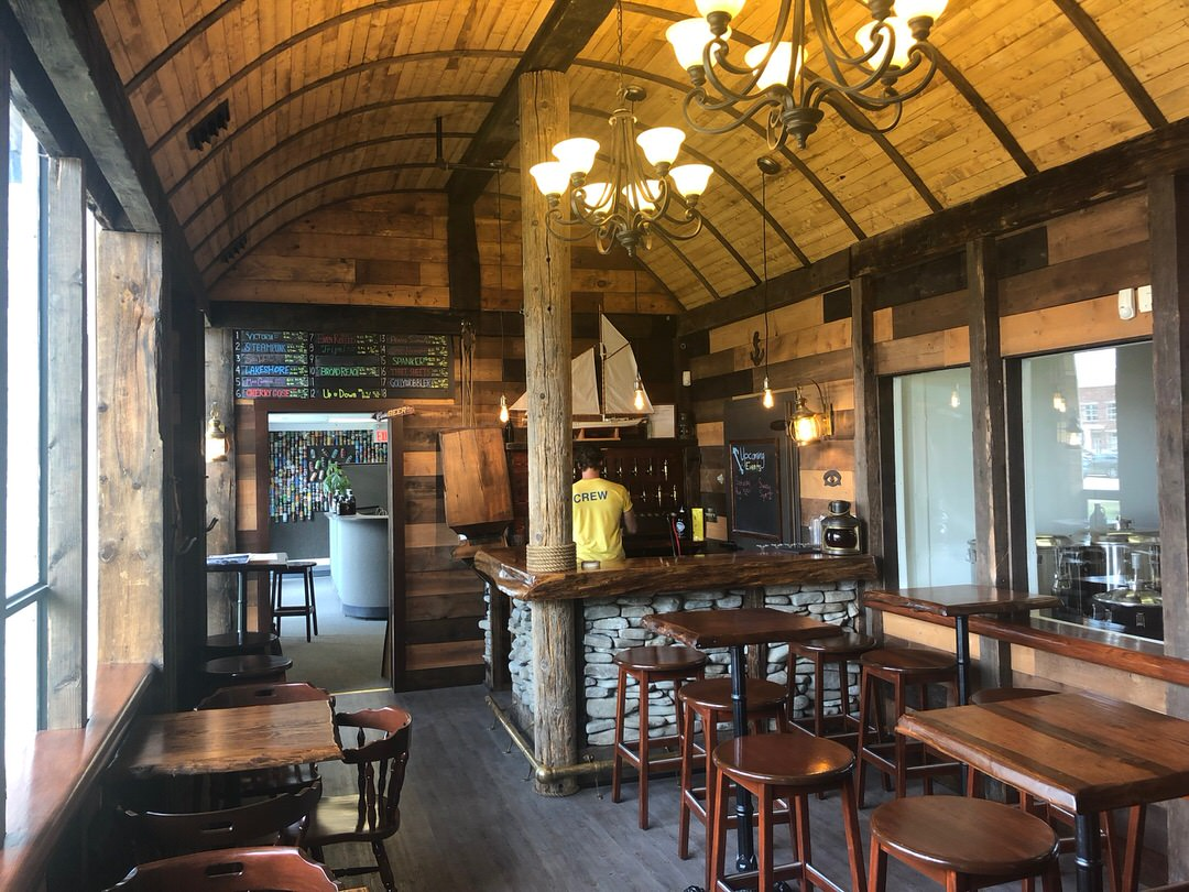 Rustic wood restaurant with wood tables and stools and chairs and bar at back corner with employee facing shelves of bottles