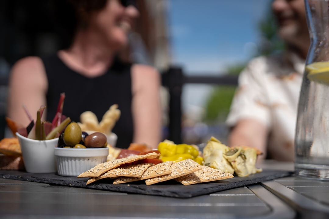 Black tray with small dishes of rhubarb and olives and crackers and finger foods beside tall bottle of water with lemon slices