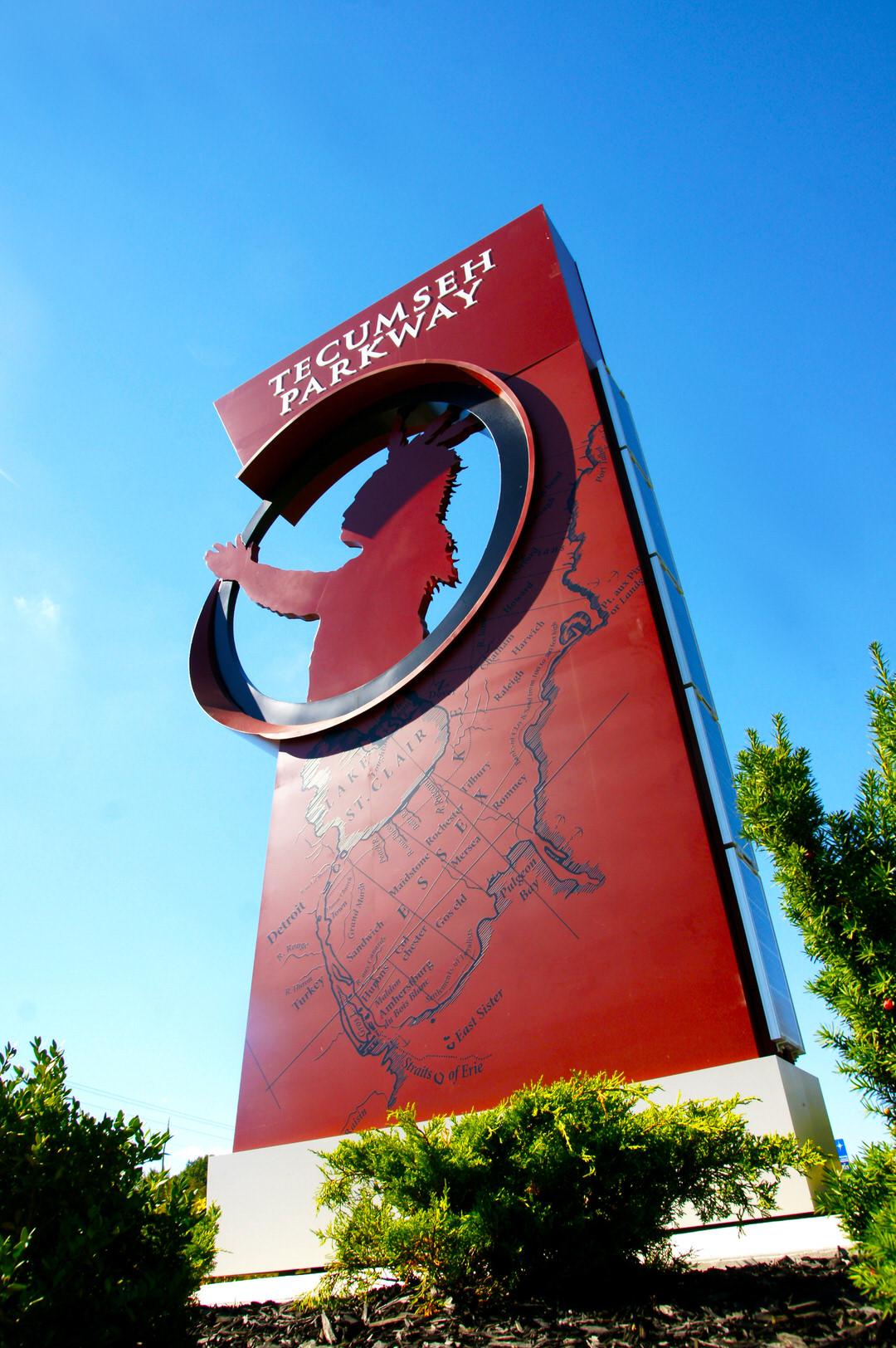 Énorme affiche rouge illustrant une carte du canton et avec un cercle découpé au haut, autour de la silhouette sculptée d'un chef autochtone avec coiffe.