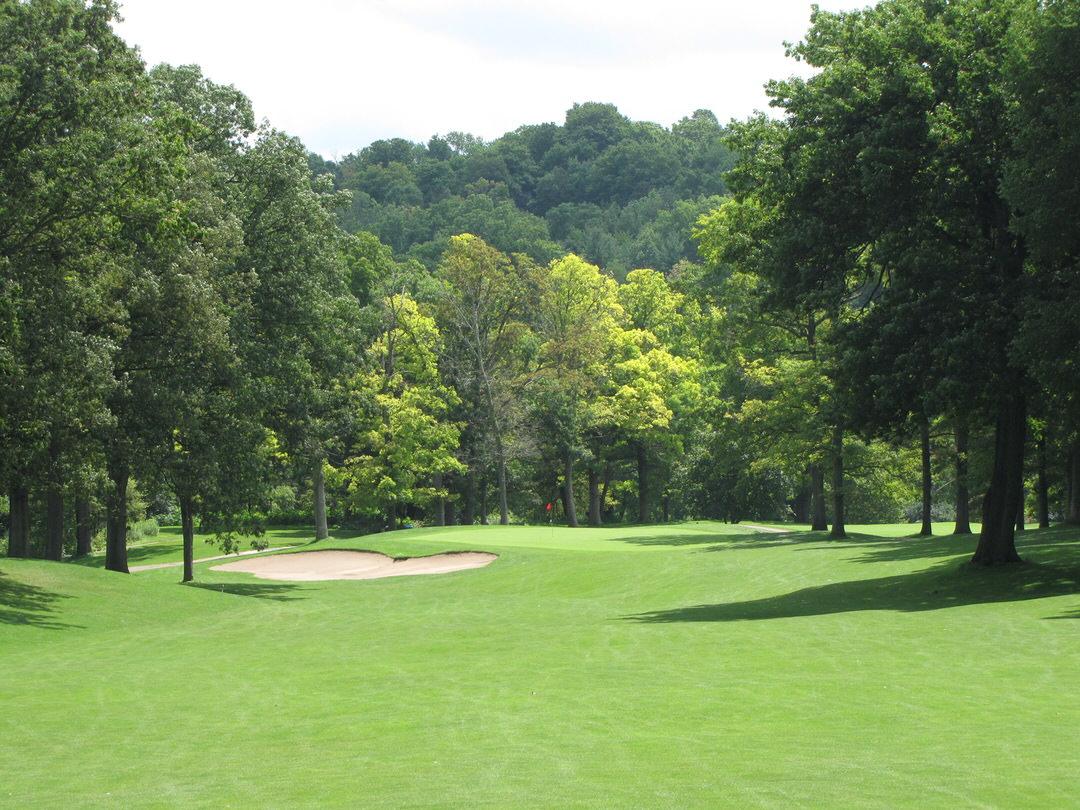 Vaste pelouse verte de terrain de golf avec trappe de sable devant un passage à l'avant-plan et une vaste forêt verte au loin.