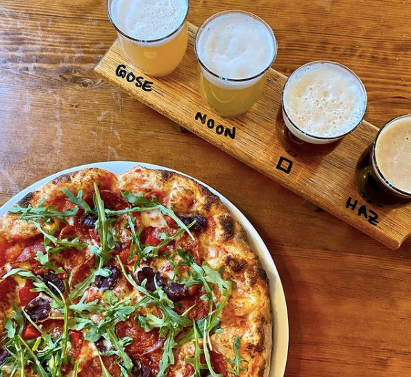Whole pizza on plate beside board holding row of 4 glasses of beer in various colours with type of beer printed on board