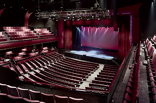 Rows of wine-coloured seats in theatre on both main floor and balconies facing empty stage with entire room softly lit