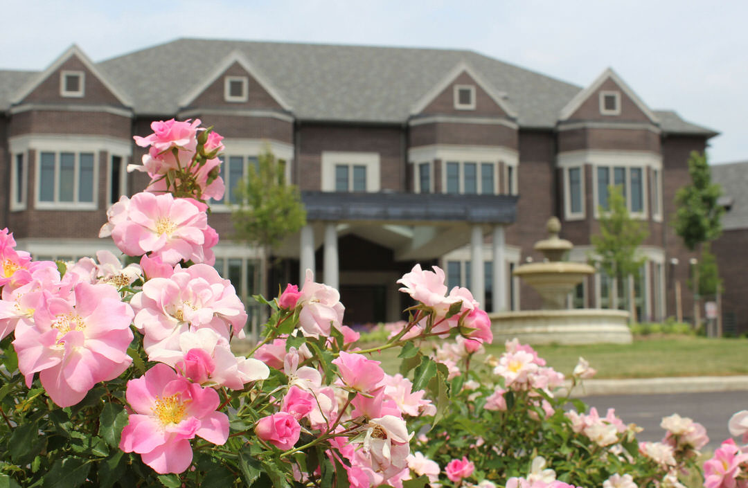Pink flowers in foreground and on far side of street large heritage hotel with round stone fountain on front lawn