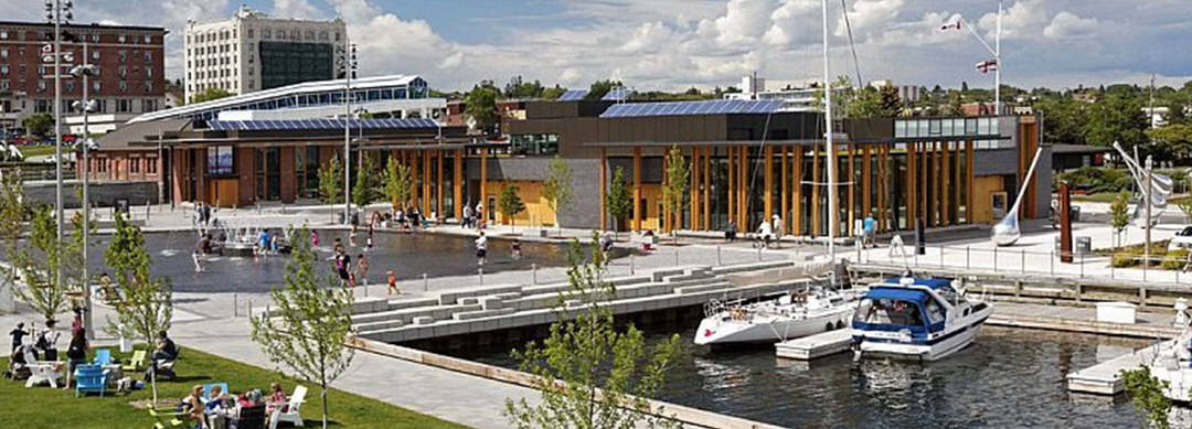 A waterfront full of people lounging, walking and wading in a fountain pool, including an area to dock boats, with access to a community building