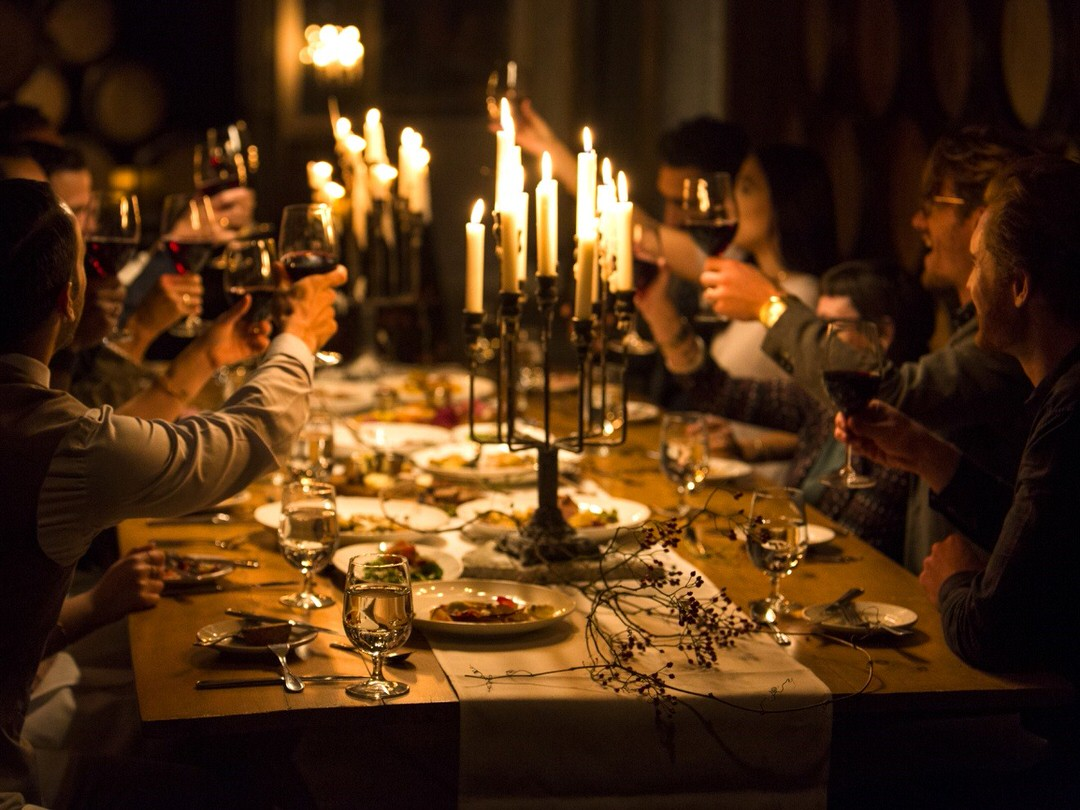 A group of friends toast with wine at a candlelit table