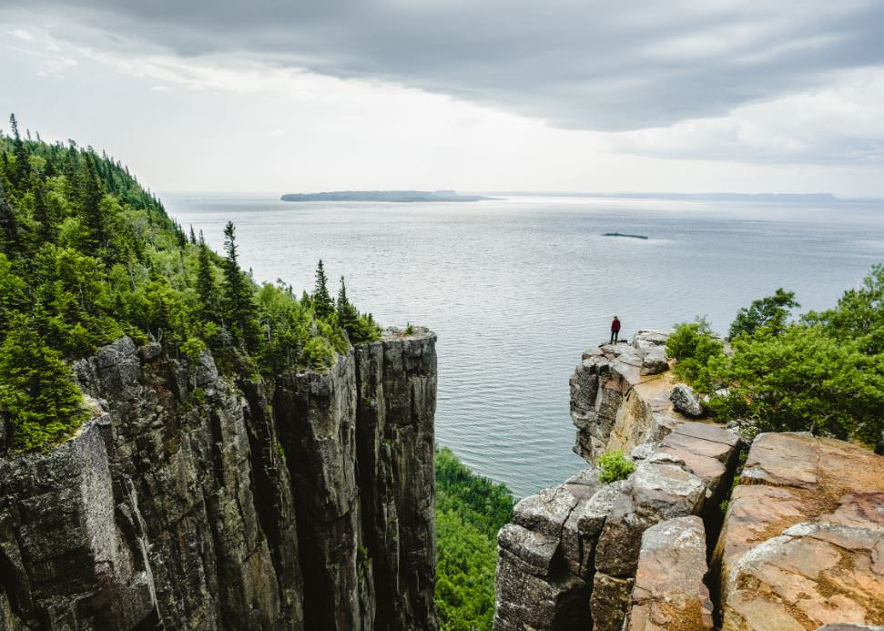 A man on the edge of a cliff admiring the landscape
